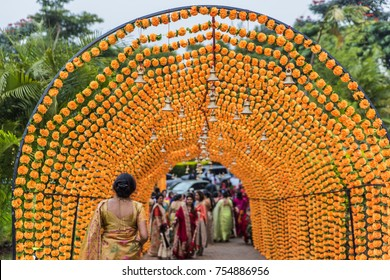 Kenya Nairobi, Aug 14 2017: Hostess walks under Hindu Wedding Arch of orange marigolds and brass bells to greet guests for traditional Indian pre wedding ceremony. Arch covers pathway away from venue.