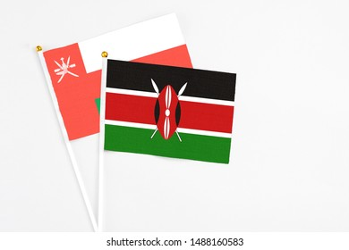 Kenya and Oman stick flags on white background. High quality fabric, miniature national flag. Peaceful global concept.White floor for copy space.