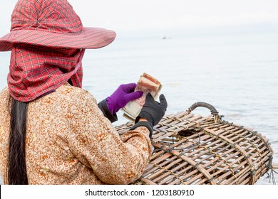 Kep, Cambodia - May 25, 2014: A Crab seller woman counting her daily earned money at Crab Market in Kep, Cambodia.