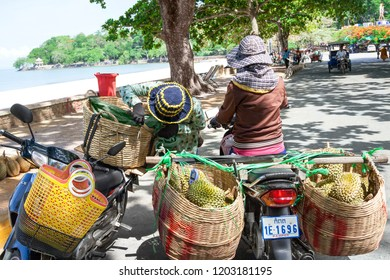 Kep, Cambodia - May 25, 2014: Two Cambodian women transporting durian fruit for sale by motorbike - close view.