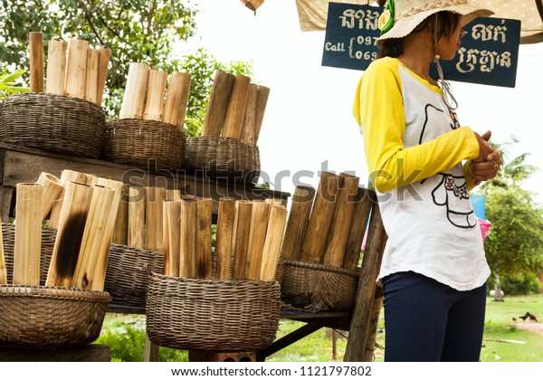 Kep, Cambodia - October 03, 2013: A gil selling local Cambodian food specialty (Kralan) - Bamboo sticks filled with sticky rice beans and grilled over open fire near Kep, Cambodia