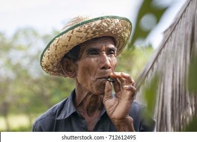 KEP CITY, CAMBODIA - May 14, 2012: Kampot farmer smoke his tobacco at his farm in Kep province