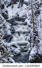 Keplar Cascades flow through snowy scenery in Yellowstone
