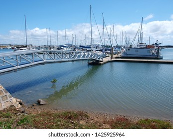 Keppel Bay Marina. Waterfront walkway with boats in tropical water with blue sky backdrop. Safe haven for sailing and cruising vessels. Queensland, Australia.