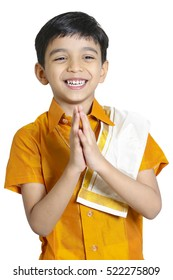 Kerala boy with traditional Indian greeting 'Namaste' on an white background , he is wearing yellow silk shirt and towel on his shoulder .