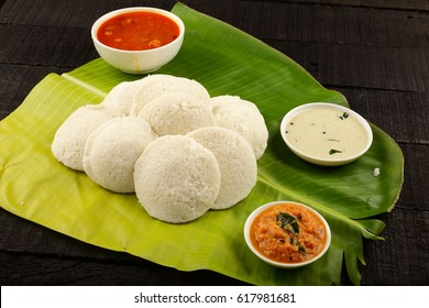 Kerala cuisine-Soft white rice iddlly spicy sambar and coconut chutneys served on banana leaf.