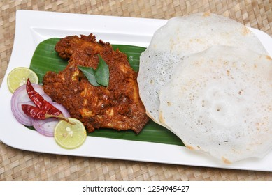 Kerala fish curry, Karimeen Pollichathu a hot and spicy baked fish in banana leaves with palappam Alleppey India.  pearl spot fish is marinated with Indian spices, wrapped in plantain leaf and grilled