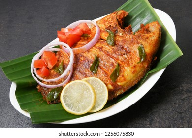 Kerala fish curry, Karimeen Pollichathu a popular hot and spicy baked fish in banana leaves Alleppey India.  pearl spot fish is marinated with Indian spices then wrapped in plantain leaf and grilled.