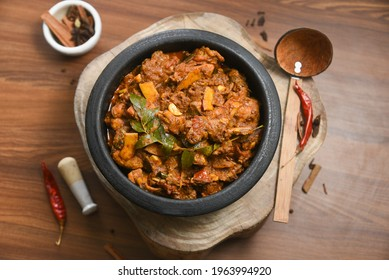 Kerala food nadan spicy chicken curry also a popular Sri Lankan food kalupol chicken curry Devilled Chicken side dish or Chettinad chicken curry with coconut pieces , Tamil Nadu India in clay pot.