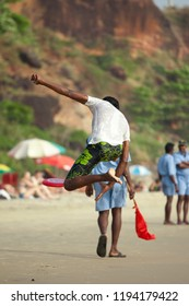 Kerala, India - 01.02.2011: A young Indian man jumps to catch a frisbee on the beach with coastguards and beachgoers in the background