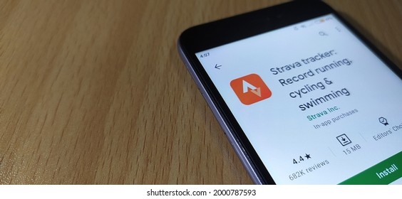 Kerala, India 01-Jun-2021 strava tracker record running cycling and swimming app on google play store opened in mobile phone device on a wooden table background surface with copy space. closeup view.