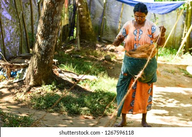 Kerala, India, circa 2019. Front view of an old woman making coir from coconut in a coir factory in a village.