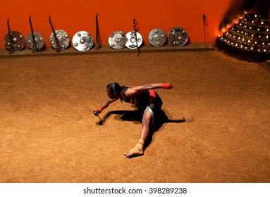 KERALA, INDIA - JANUARY 18, 2016: Indian fighter performing Kalaripayattu marital art  in Kerala, India. Kalaripayattu is an ancient form of martial art of Kerala dating back to almost 2000 years.