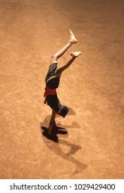 KERALA, INDIA - NOVEMBER 11, 2016: Young Indian student of Kalarippayattu school doing handstand and demonstarate his skills. Kalaripayattu is an ancient form of martial art of Kerala