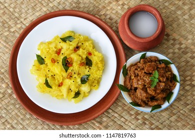Kerala special Kappa Puzhukku prepared with grated coconut South Indian food with  spicy meat curry, palm wine or toddy,  India. Cooked tapioca or Cassava root, Mandioca or Aipim root vegetable Brazil