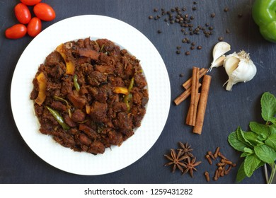 Kerala style beef dry fry. delicious spicy Beef fry in white plate background. It goes well with ghee rice, kappa,appam, parotta, puttu, bread and chappathi, Kerala style cuisine ,beef roast.India