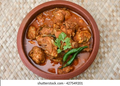 Kerala style food hot spicy red Asian chicken curry with thick gravy. famous breakfast dish in mud or clay pot . Indian food culture in earthen pot.