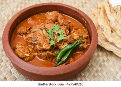 Kerala style food hot spicy red Asian chicken curry having thick gravy with Kerala porotta / paratha / roti / naan . famous breakfast dish in mud or clay pot . Indian food culture in earthen pot.