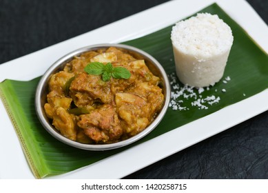 Kerala style Kozhi Pidi or Kunji Pathal soft rice dumplings cooked in roasted coconut chicken or mutton curry with Puttu. Popular meal, snack or side dish on green banana leaf background Kerala India.