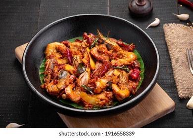 Kerala style Prawns roast or chemmeen varattiyathu  using red kashmiri chilli flakes and coconut slices as main ingrediants and garnished with onion rings and tomato slices ,placed on a black texture