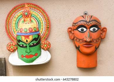 kerala traditional Kathakali dancer Wall art  Display of colorful souvenirs beautiful human / womans / wooden carving of staring face wearing ornaments  made of wood in Delhi, India.