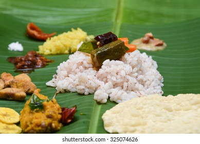 Kerala Traditional Onam sadhya, boiled rice served with curries Parippu, Sambar, Rasam, Pulisseri, Kaalan, Avial, Thoran, Olan, Pachadi, Naranga, Papadum, Payasam, Banana, Yogurt or Buttermilk, chips.
