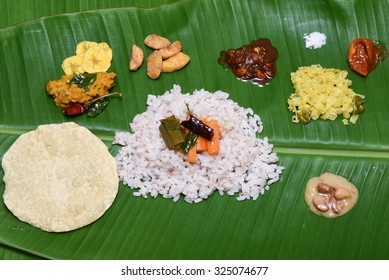 Kerala Traditional Onam sadhya, boiled rice served with curries Parippu, Sambar, Rasam, Pulisseri, Kaalan, Avial, Thoran, Pachadi, Naranga, Papadum, Payasam, Banana, Yogurt or Buttermilk, chips. Vishu