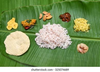 Kerala Traditional Onam sadhya, boiled rice served with curries Parippu, Sambar, Rasam, Pulisseri, Kaalan, Avial, Thoran, Olan, Pachadi, Naranga, Papadum, Payasam, Banana, Yogurt or Buttermilk, chips.