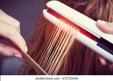 Keratin recovery and protein treatment with professional ultrasonic iron tool. Concept of trendy laminating and strengthening care for healthy hairs
