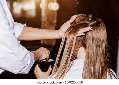 Keratin restoration, hair care concept. Beautician apply balm and conditioner to the hair of woman after haircut. Close up of female hairdresser's hands dyeing hair in beauty salon.