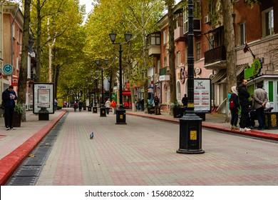 Kerch, Crimea, Russia - September 25, 2019: City Center. Pedestrian street of Lenin. Warm autumn day. People walk along shady plane tree alley on pedestrian street.