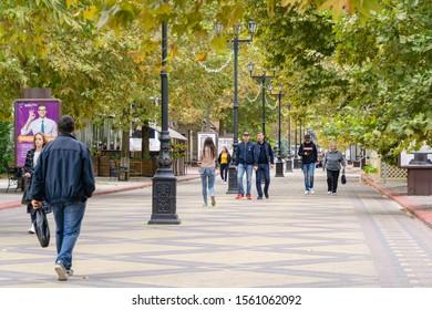 Kerch, Crimea, Russia - September 25, 2019: Pedestrian Lenin Street in center of Kerch city. People calmly walk along shady alley of tall plane trees. Warm autumn day