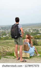 KERCH, CRIMEA - SEPTEMBER 23, 2018: Young couple admires city view from Mithridates mountain. Girl in  beautiful blue sundress with leather backpack on her back is sitting on stone, guy stands nearby