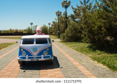 KERCH, RUSSIA - JUNE 1, 2018: a little girl rides on toy electric cars blue in the park for children's day.