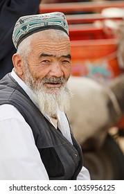 Keriya,China - October 04,2017: Uyghur elder sells his merchandise in the local market on October 04, China.