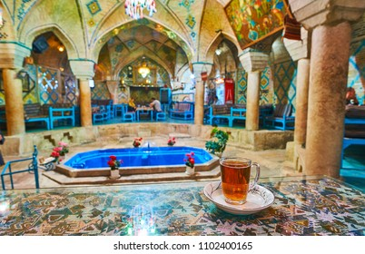 KERMAN, IRAN - OCTOBER 15, 2017: The cup of Persian tea on the table in Vakil restaurant and teahouse, located in building of the former bath with splendid historical interior, on October 15 in Kerman