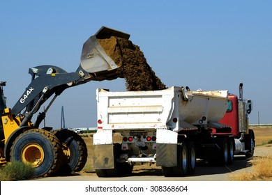 KERN COUNTY, CA - AUG 20, 2015: A front end loader discharges excess dirt from a construction project into a bottom dump truck which will take the material off site.