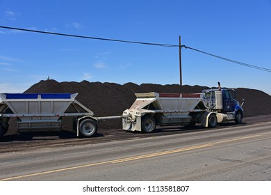 KERN COUNTY, CA - JUNE 15, 2018: A bottom dump trailer deposits oil sand on the ground to be pushed into a pile by a bucket loader. It will be used for road repairs in the county.