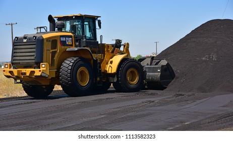 KERN COUNTY, CA - JUNE 15, 2018: A bucket loader pushes oil sand into a large pile. It will be used for road repairs throughout the county.