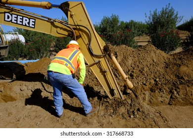 KERN COUNTY, CA - SEPTEMBER 17, 2015: The foreman on a sewer installation project closely inspects the trench made by a backhoe prior to burying the pipe.