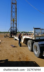 KERN COUNTY, CA - SEPTEMBER 17, 2015: Roughnecks  untie a load of sucker rods on a flatbed trailer as they prepare to set up their servicing rig over an existing oil well.
