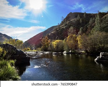 Kern river in Kernville California fall colors on leaves with the sun in the sky and a lens flare river in foreground