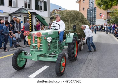 Kerns, Switzerland - 1 October 2016: Man driving a tractor on at the traditional rural transhumance parade of Kerns on the Swiss alps