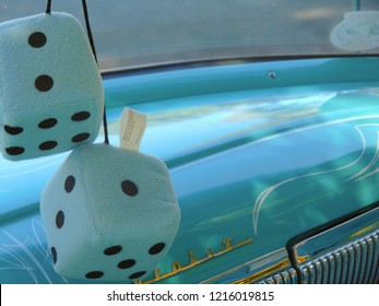 Kernville, California / USA - October 7, 2016: White fuzzy dice hanging from the rear view mirror of an aqua colored Chevrolet Bel Air at the Kernville Classic Car Show, with pinstriped dashboard