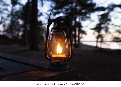 Kerosene lamp at the lakeside. Beautiful colorful illuminated lamp in the forest in misty night. Vintage style lantern at night outdoor.