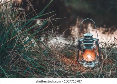 Kerosene lamp on the background of the lake and nature.