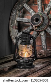 kerosene lamp on the old wooden boards against the background wagon wheel