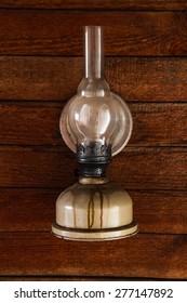 Kerosene lamp on a wooden wall. Vintage toning