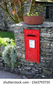 Keswick, Cumbria, UK - April 6th 2019: Old vintage British Georgian letter box, mounted into a dry stone wall in the English Lake District
