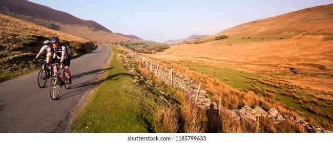 Keswick, England, UK - April 20, 2009: Two cyclists climb a narrow country lane through the mountain moorland landscape of the Newlands Valley in England's Lake District National Park.